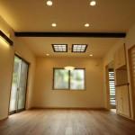 天窓からたっぷりの太陽光が降り注ぐ明るいリビングルーム。 天然唐松の無垢フローリングにけいそう土の塗り壁、木の梁など・・・ 自然の恵みをたっぷりと詰め込んだ家族団らんのスペースです。