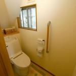 トイレ:階段下のスペースを利用したトイレ。天井が低いところには棚をつけて広く感じる工夫をしています