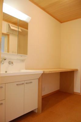 洗面所:シンプルな洗面化粧台と何かと便利に使える大きな木のカウンター。カウンター下に引き出しを置けば、タオルや下着などがたくさん収納できます。あとはK様の工夫次第。