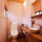 トイレ1:木楽オリジナルの手洗いカウンターと小物たち。ケイソウ土の壁には奥様と一緒に拾った小石が散りばめられています。