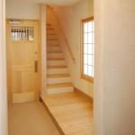 玄関2:普段の出入りはガレージから倉庫を通り抜けて玄関に通じます。玄関ドアは無垢の木(ヒバ)を使った木楽オリジナル。床は3.5㎝もある分厚い床板を縁側風に張っています。素足で上がるとその床板(イエローパイン)のしっとりとした感触がたまらなく気持ち良いです。