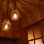 ホール3:ひび割れガラスの照明を2種類段違いでぶら下げたら、こんなに可愛くなりました。ガラスを通した明かりがケイソウ土の壁と天井をキラキラと照らしています。