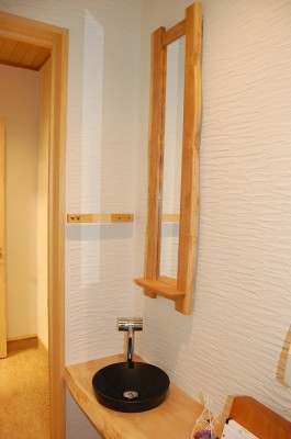 無垢の木のカウンターと陶器の手洗い器。木の鏡と木楽スタッフ手づくりのタオル掛け。