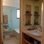 洗面所:クスの無垢板でつくったオリジナルのカウンター。鏡と照明は再利用したECOリフォーム。